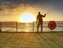 Tourist on ferry boat mole within sunrise or sunset. Warm colors royalty free stock images