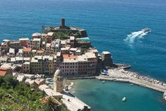 Tourist Ferry Departing from Vernazza on a Sun-Drenched Mediterranean Day. A passenger ferry leaves Vernazza in the Cinque Terre in Italy, with the village Royalty Free Stock Photos