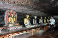 Tourist the figures of Buddha in the cave temple of Dambulla. Stock Image