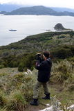 Tourist is filmed on the island of Navarino in Murray Channel in Tierra del Fuego. Stock Photos