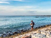 Tourist fishing off the rocks in Kuta Bali stock photography
