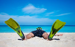 Tourist with flippers laying on sand beach Stock Photos