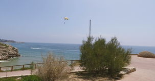 Tourist. flying under a parachute. is towed from right to left across the frame in the sea. Tourist. flying under a parachute. is towed from right to left across stock video footage