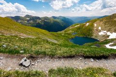 Tourist foot path in Fagarasan mountains, Romania. Gorgeous view from the hillside in to the distant valley. lake Capra down the grassy slope. amazing summer Royalty Free Stock Photo