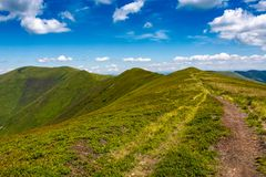 Tourist footpath through mountain ridge. Beautiful summer landscape under the gorgeous blue sky with some clouds Royalty Free Stock Photography