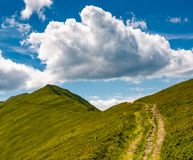 Tourist footpath through mountain ridge. Beautiful summer landscape under the gorgeous blue sky with some clouds Royalty Free Stock Image
