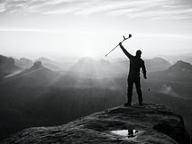 Tourist with forearm crutch above head achieved mountain peak. Hiker with broken leg. In immobilizer and medicine poles hold hand in air. Colorful misty valley Royalty Free Stock Images