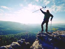 Tourist with  forearm crutch above head  on trail. Hurt hiker achieved mountain peak. With broken knee in immobilizer.  Deep valley bellow silhouette of man Royalty Free Stock Images