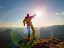Tourist with  forearm crutch above head  on trail. Hurt hiker achieved mountain peak. With broken knee in immobilizer.  Deep valley bellow silhouette of man Royalty Free Stock Photography
