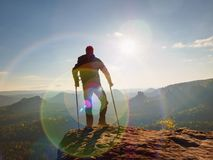 Tourist with  forearm crutch above head  on trail. Hurt hiker achieved mountain peak. With broken knee in immobilizer.  Deep valley bellow silhouette of man Stock Photography
