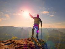 Tourist with  forearm crutch above head  on trail. Hurt hiker achieved mountain peak. With broken knee in immobilizer.  Deep valley bellow silhouette of man Stock Image