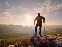 Tourist with  forearm crutch above head  on trail. Hurt hiker achieved mountain peak. With broken knee in immobilizer.  Deep valley bellow silhouette of man Stock Images