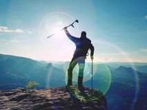 Tourist with  forearm crutch above head  on trail. Hurt hiker achieved mountain peak. With broken knee in immobilizer.  Deep valley bellow silhouette of man Royalty Free Stock Photos