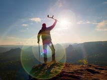 Tourist with  forearm crutch above head  on trail. Hurt hiker achieved mountain peak. With broken knee in immobilizer.  Deep valley bellow silhouette of man Stock Photo