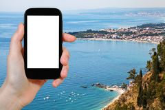 Tourist fotografiert Küstenlinie mit Giardini Naxos Stockbilder