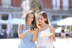 Tourist friends consulting an online guide Royalty Free Stock Images