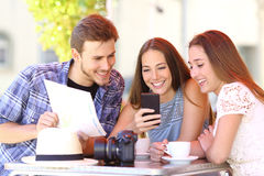 Tourist friends planning vacation with gps phone Stock Image