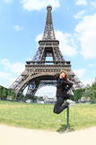 Tourist in front of Eiffel tower. Papuan tourist girl - young smiling woman jumping in front of Eiffel tower in Paris (France Royalty Free Stock Images