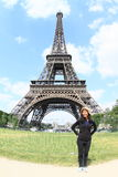 Tourist in front of Eiffel tower. Papuan tourist girl - young smiling woman standing in front of Eiffel tower in Paris (France Royalty Free Stock Images