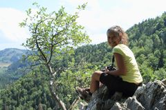 Tourist in front of forest hills in Slovak Paradise. Papuan young tourist woman - smiling tropical girl sitting on edge of viewpoint to hills with forest in stock images