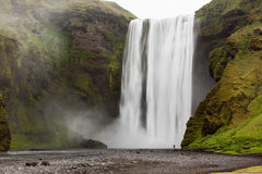 Tourist in front of Skogafoss waterfall Royalty Free Stock Photos
