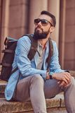 Tourist with a full beard and haircut, wearing casual clothes with a backpack and sunglasses, sitting on a step in an. A tourist with a full beard and haircut Royalty Free Stock Photos