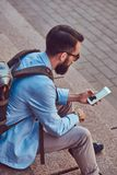 Tourist with a full beard and haircut, wearing casual clothes with a backpack, texting on a smartphone, sitting on a. A tourist with a full beard and haircut Stock Photography