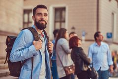 Tourist with a full beard and haircut, wearing casual clothes, holds a backpack and texting on a smartphone, standing on. A tourist with a full beard and haircut Stock Photography