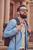 Tourist with a full beard and haircut, wearing casual clothes and sunglasses, holds a backpack, standing on an antique. A tourist with a full beard and haircut Stock Photo