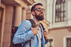 Tourist with a full beard and haircut, wearing casual clothes and sunglasses, holds a backpack, standing on an antique. A tourist with a full beard and haircut Royalty Free Stock Photography