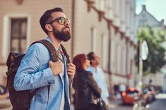 Tourist with a full beard and haircut, wearing casual clothes and sunglasses, holds a backpack, standing on an antique. A tourist with a full beard and haircut Royalty Free Stock Photo