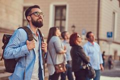 Tourist with a full beard and haircut, wearing casual clothes and sunglasses, holds a backpack, standing on an antique. A tourist with a full beard and haircut Stock Photos