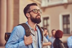 Tourist with a full beard and haircut, wearing casual clothes and sunglasses, holds a backpack, standing on an antique. A tourist with a full beard and haircut Royalty Free Stock Image