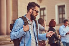 Tourist with a full beard and haircut, wearing casual clothes and sunglasses, holds a backpack and texting on a. A tourist with a full beard and haircut, wearing Royalty Free Stock Photography