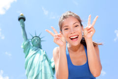 Tourist funny at Statue of Liberty, New York, USA. Tourist at Statue of Liberty, New York, USA making funny face expression victory hand signs excited and happy Stock Image