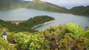 Tourist geht einen Gebirgsweg in der dichten Vegetation mit einem schönen Seeblick im Krater eines Vulkans hinunter stock video footage