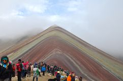 Tourist get a glimpse of Vinicunca Rainbow Mountain in Peru through the clouds.