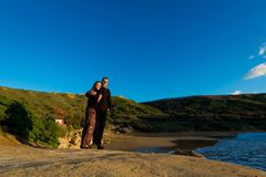 Tourist on Ghajn Tuffieha Bay. Young couple of tourists on beautiful Ghajn Tuffieha Bay taken during colorful sunset on Malta island. Beautiful landscape in Stock Photos