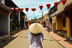 Woman with vietnamese hat in the historic street of Hoi An Vietnan. Tourist girl in the Ancient city of Hoi An with a traditional hat. Lanterns. Asia. Bridge royalty free stock image