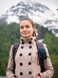 Tourist girl with a backpack on the backdrop of snow-capped mountains stock photos