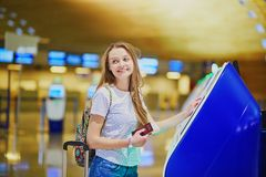 Tourist girl with backpack and carry on luggage in international airport, doing self check-in Stock Photo