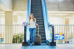 Tourist girl with backpack and carry on luggage in international airport, on escalator Royalty Free Stock Photo