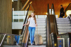 Tourist girl with backpack and carry on luggage in international airport, on escalator Royalty Free Stock Images