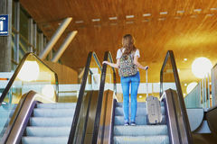 Tourist girl with backpack and carry on luggage in international airport, on escalator Stock Image