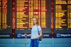 Tourist girl with backpack and carry on luggage in international airport, near flight information board Stock Photo