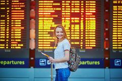 Tourist girl with backpack and carry on luggage in international airport, near flight information board Royalty Free Stock Image