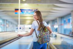 Tourist girl with backpack and carry on luggage in international airport, on travelator Royalty Free Stock Photography