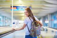 Tourist girl with backpack and carry on luggage in international airport, on travelator Stock Photo