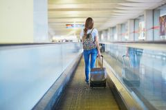 Tourist girl with backpack and carry on luggage in international airport, on travelator Stock Images