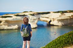 Girl enjoying view to sea coast in Sardinia, Italy. Tourist girl with backpack enjoying beautiful view of natural arch and sea in Sardinia, Italy Stock Images